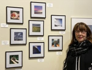 The image shows Sandy Brown Jensen with her exhibit at the opening of the PhotoZone Dec. 2019 show