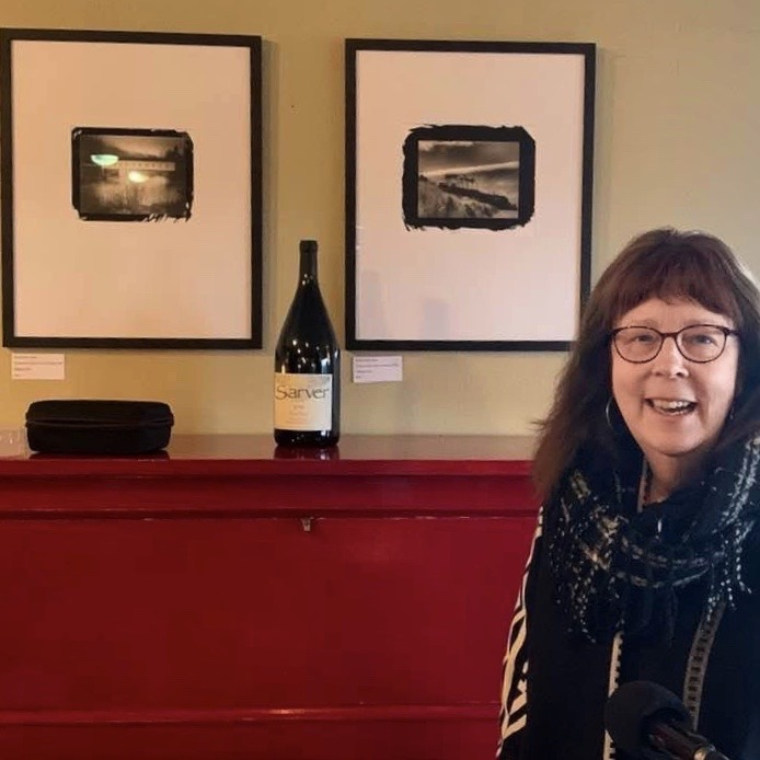 Sandy at the Sarver Winery in front of her two photos